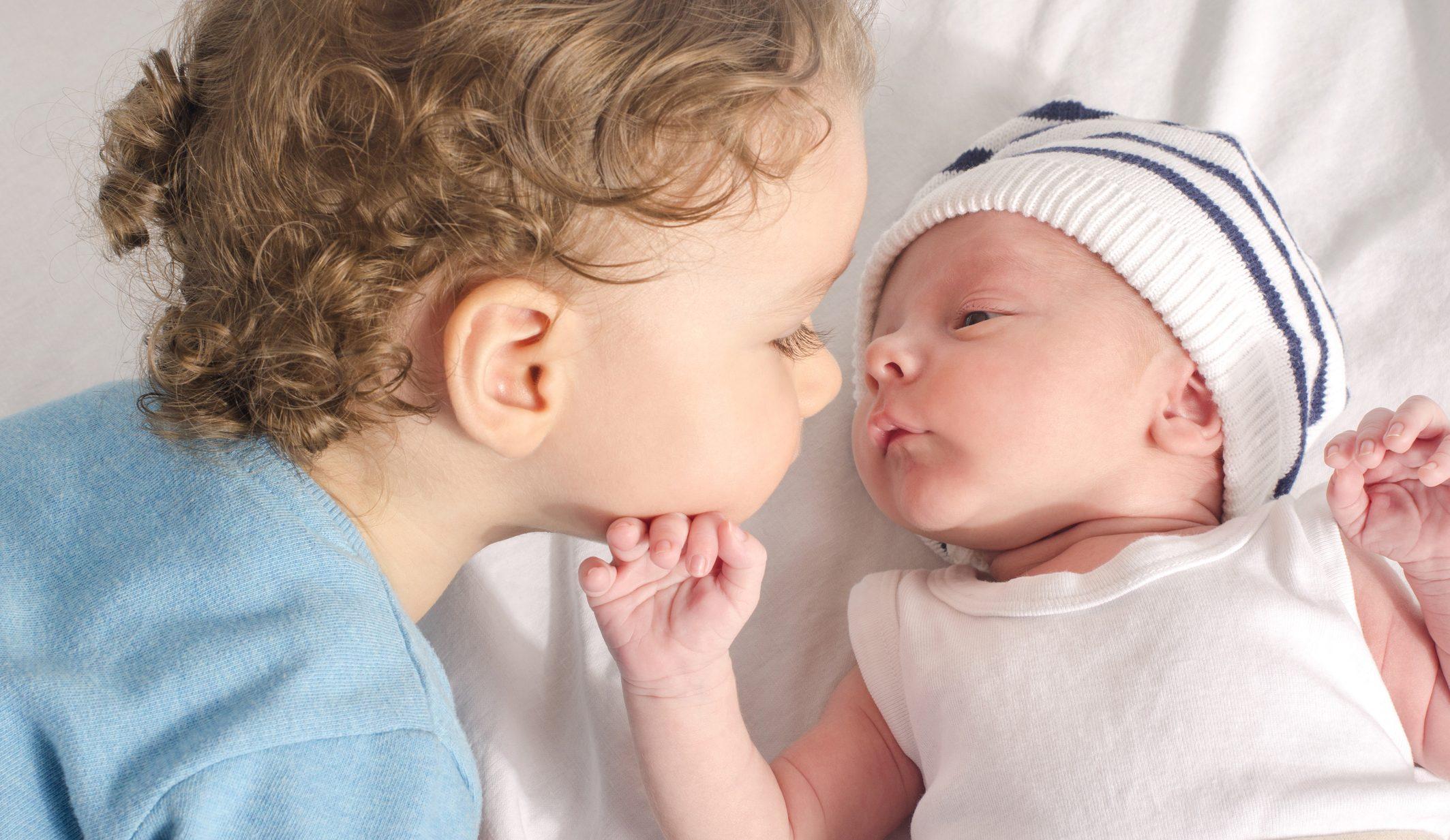 Big brother kissing baby sibling.